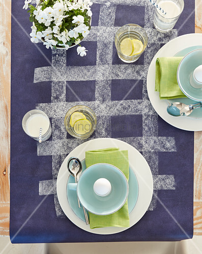 Place settings with boiled eggs on purple tablecloth