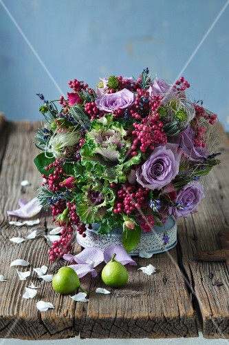 Colourful arrangement of purple roses, ornamental cabbage and pink pepper