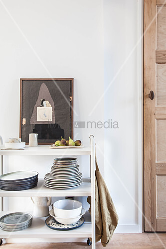 Crockery on white serving trolley and artwork next to door