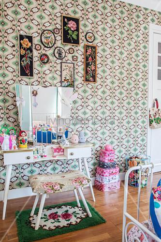 Gepolsterter Hocker, Schminktisch und Kofferstapel im Mädchenzimmer mit Retro Tapete