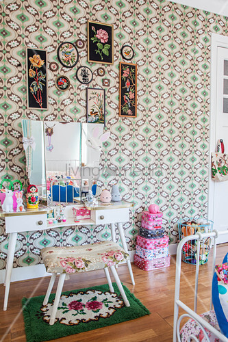 Upholstered stool, dressing table and stacked suitcases in girl's bedroom with retro wallpaper