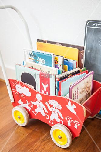Retro Puppenwagen aus Holz als Aufbewahrung für Bücher