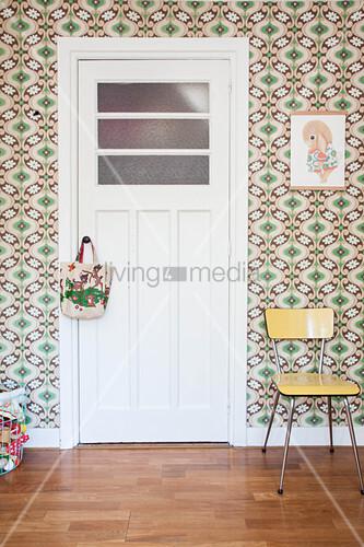 White interior door in room with retro wallpaper