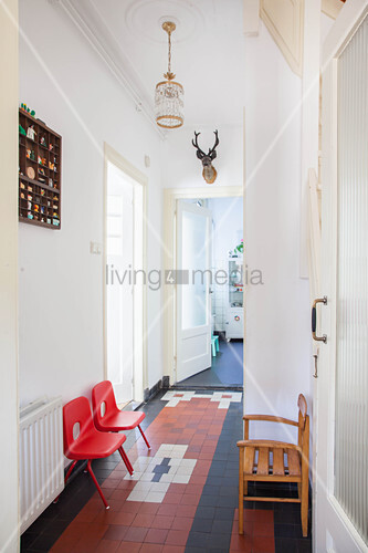 Two red plastic chairs and wooden chair in corridor of period apartment