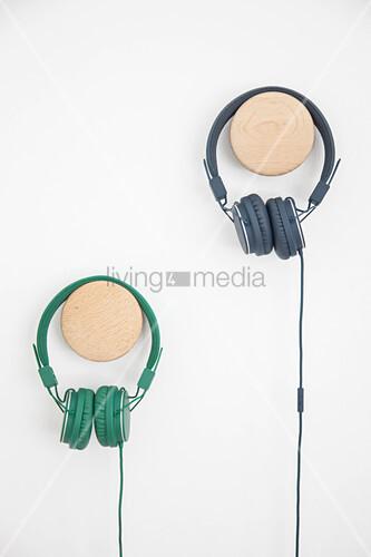 Headphones on wooden pegs on wall