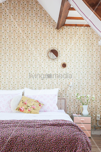 Double bed in bedroom with retro wallpaper