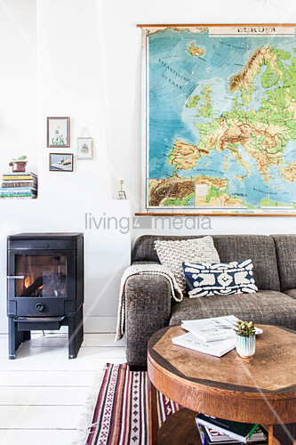 Log burner next to sofa and coffee table in living room with white wooden floor