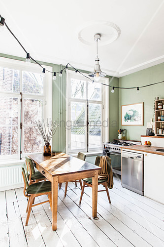 Green wall, white wooden floor and dining set in front of large windows in kitchen-dining room