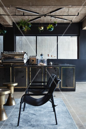 Black armchair and gilt side tables in front of bar