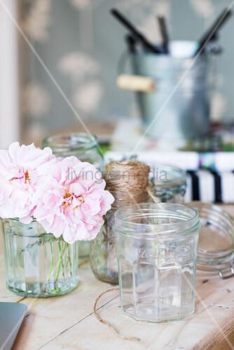Einmachglas und rosa Blume auf Holztisch