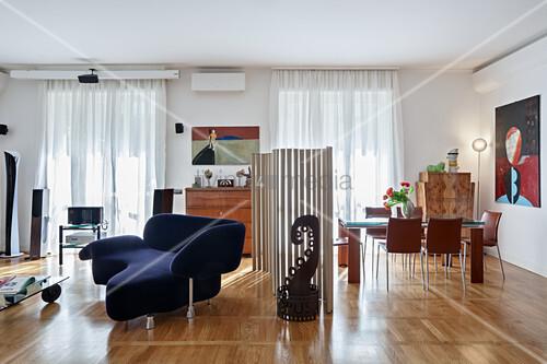 Designersofa und Essbereich, geteilt durch Paravent aus Pappröhren in offenem Wohnraum