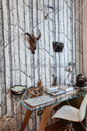 Desk with glass top and designer chair against tree-patterned photo wallpaper