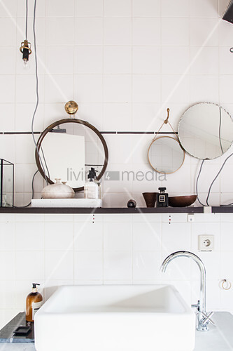 Washstand with countertop sink below shelf in white bathroom