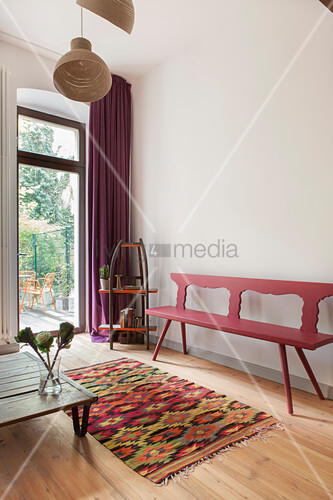 Red-painted wooden bench, vintage shelves, low coffee table and colourful rug in front of terrace doors in living room
