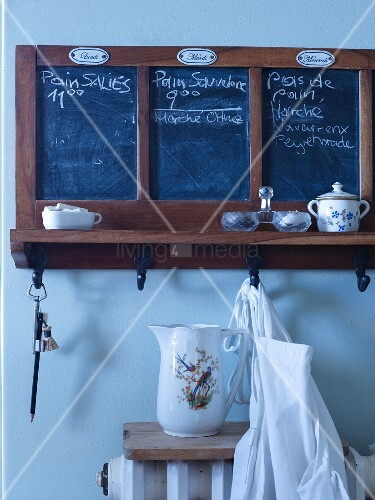 Chalkboards and hooks for weekly planning on old wall-mounted shelf