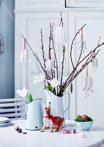 Äste mit Stoffblüten als Anhänger und weiße Tulpen in Kurgvase