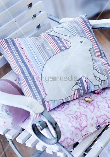Easter-bunny cushion and chocolate eggs on vintage chair