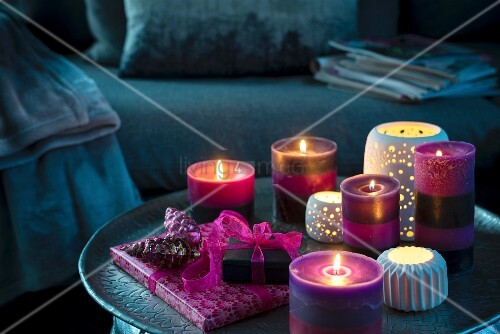 Purple candles, tealights and gifts on dark coffee table