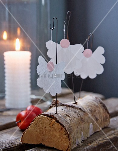 Paper angels on wire hooks stuck in birch log