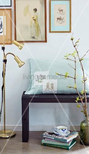 Kissen mit bestickten Aufnähern auf einer Bank an der Bilderwand