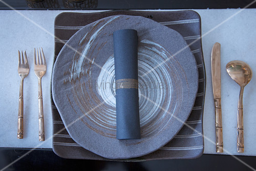 Gold cutlery and round plate on square charger plate in shades of grey