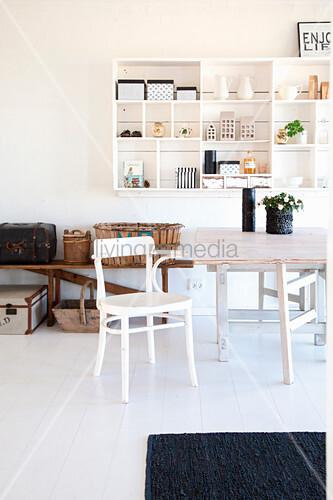 Holztisch und Stuhl vor Bank mit Koffern und Körben und weißem Wandregal