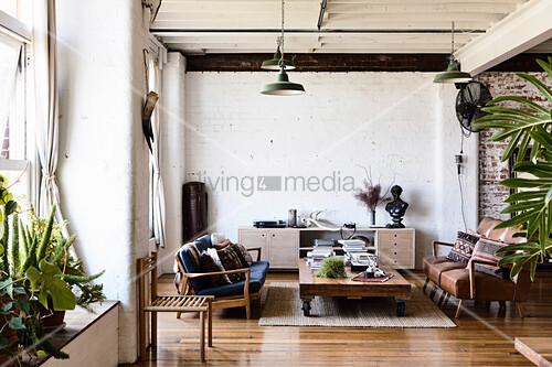 Wohnzimmer mit Vintagemöbeln im Loft mit weißer Backsteinwand
