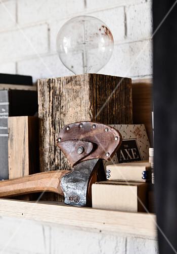 Axt in einer Lederscheide und Leuchte im Holzblock im Bücherregal