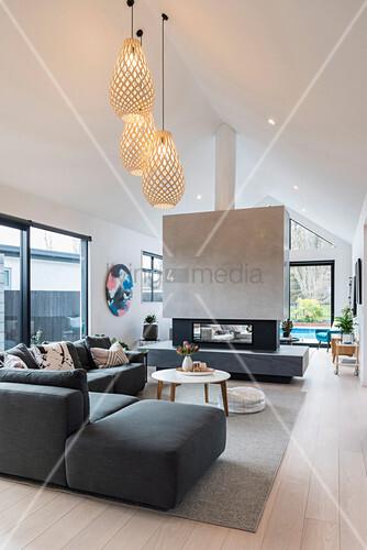 Kamin in einer Raumteilerwand im Wohnzimmer mit Giebeldach