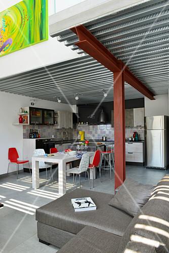 Wohnbereich mit grauer Couch und Küche und Essbereich mit Designerstühlen im Industrie-Loft