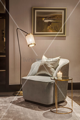 Atmospheric lighting around armchair and small gilt side table