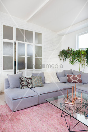 Grey corner sofa with scatter cushions, coffee table with glass top and plants on windowsill in front of interior doors with glass panels