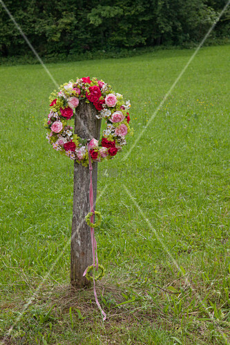 Wreath of roses and lady's mantle hung from wooden post in garden