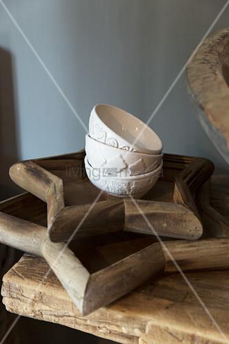 weiße Schälchen mit Relief auf zwei sternförmigen Holztabletts