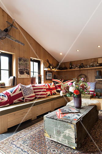 Flag-patterned scatter cushions on solid wooden corner bench in converted barn with wood-clad walls