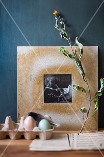 Black-and-white photo in hand-made frame, dried flowers and Easter eggs