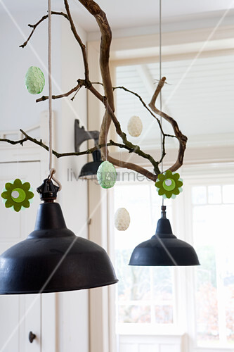 Hand-made felt flowers and Easter eggs hung from branch above pendant lamp