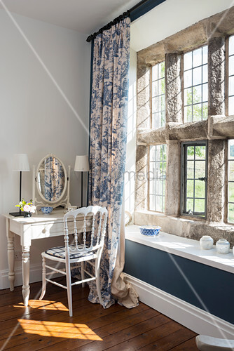 Antique dressing table and chair next to rustic stone window with modern sill and toile de jouy curtains