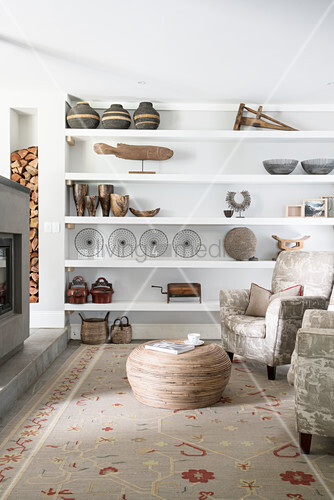 Vintage ornaments on open shelves, armchair, bamboo coffee table and log-burner in living room
