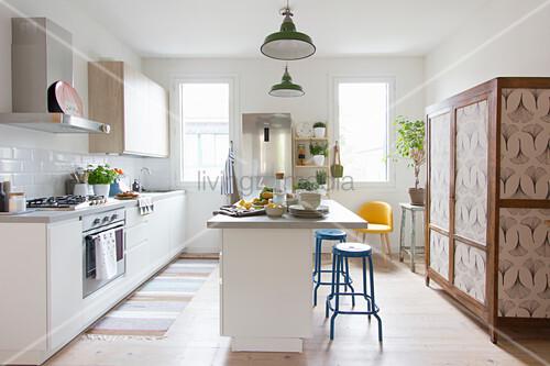 weiße Küche mit Mittelblock, blauen Barhockern und altem Schrank mit tapezierter Tür