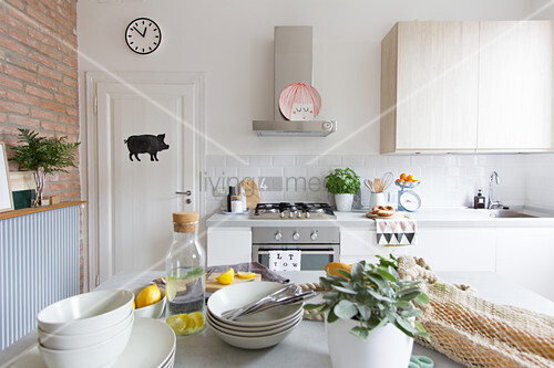 Blick über Tisch mit Geschirr auf Küchenzeile