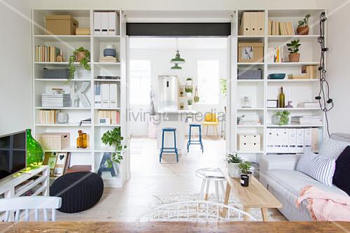 Wide open doorway between living room and kitchen flanked by floor-to-ceiling shelves