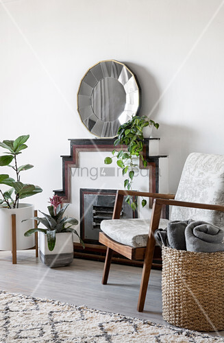 Houseplant and armchair in front of fireplace and mirror