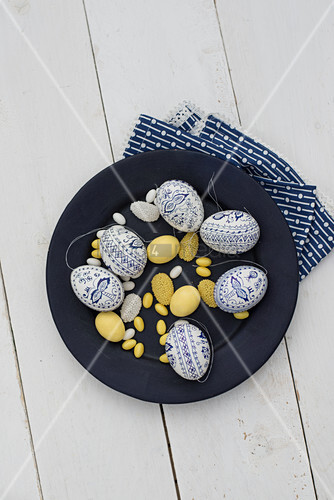 Easter eggs painted blue and white, yellow sugar eggs and marzipan eggs on plate