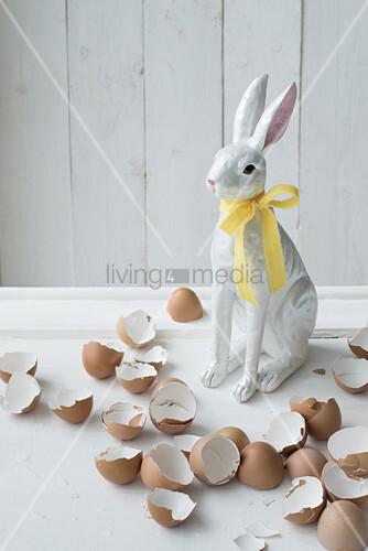 Osterhasenfigur mit gelber Schleife und Eierschalen