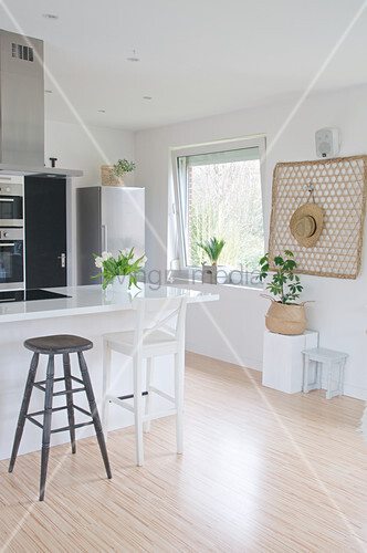 Black and white bar stools in open-plan Scandinavian-style kitchen