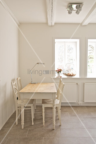 White wooden table and chairs in corner of room
