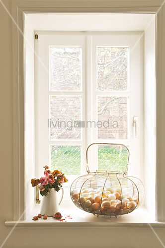 Basket of eggs and jug of dried roses on windowsill