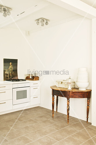 Crockery on antique console table in off-white kitchen