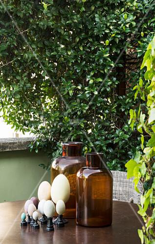 Apothekerflaschen und Eier-Sammlung auf dem Gartentisch